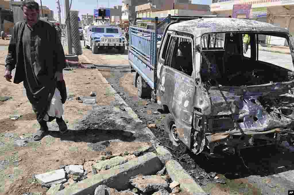 A man stands at the scene of a car bomb attack in Ramadi. (AP)