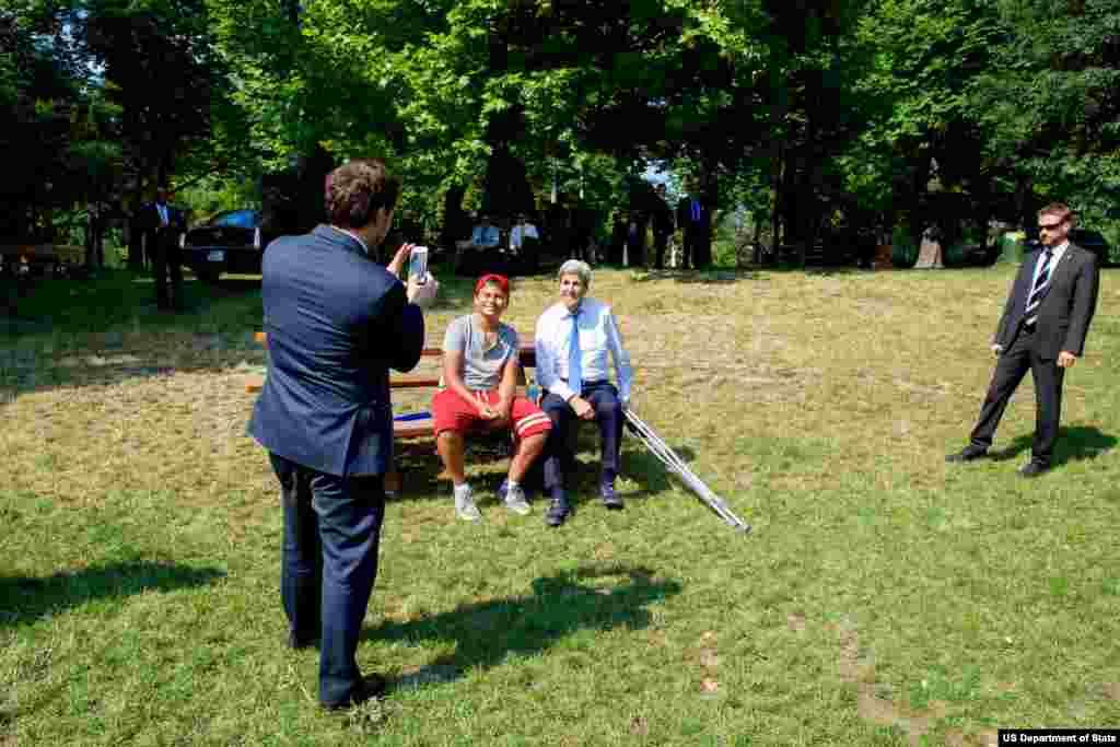 جان کری در پارک در حال عکس گرفتن با جوانی که مادرش سال گذشته در هواپیما با او همسفر بود - ۱ ژوئیه ۲۰۱۵