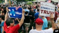 FILE - Supporters of Democratic presidential candidate Hillary Clinton and Republican presidential candidate Donald Trump hold signs at a Memorial Day parade in Chappaqua, N.Y., May 30, 2016.
