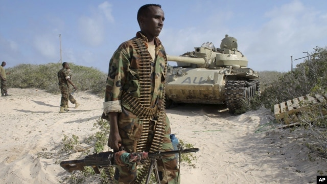 A Somali government soldier holds his weapon in the port of El-Ma'an a few hours after Somali and African Union forces ousted al-Shabab fighters from the area 32km northeast of Mogadishu, Somalia, Sept. 4, 2012. Elsewhere, the Kenyan Navy shelled Somalia's port town of Kismayo, the remaining stronghold of the al-Qaida-linked militants, in preparation for ground forces to capture the town.