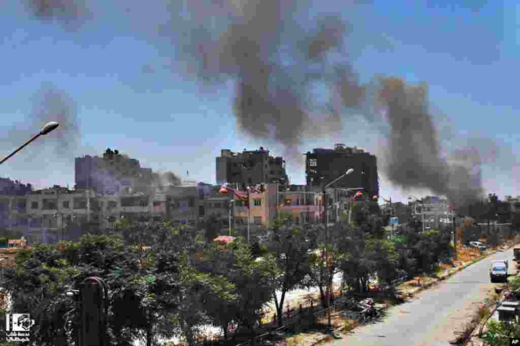 This citizen journalism image provided by Lens Young Homsi shows black smoke rising from buildings damaged by Syrian government airstrikes and shelling in Homs, Syria, July 7, 2013.