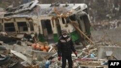 Một người đàn ông tìm kiếm thân nhân trong đống đổ nát tại một khu vực bị sóng thần tàn phá ở Onagawa, quận Miyagi, ngày 20/3/2011