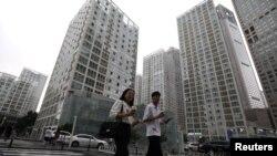 2021 年 7 月 13 日,人们走过中国北京中央商务区 (CBD) 的办公楼。
