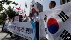 South Korean protesters shout slogans as they hold national flags during a press conference against abrupt cancellation by North Korea of planned reunions for families separated by the Korean War, Sept. 23, 2013.