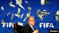 British comedian Lee Nelson (unseen) throws banknotes at FIFA President Sepp Blatter as he arrives for a news conference after the Extraordinary FIFA Executive Committee Meeting in Zurich, Switzerland, July 20, 2015.