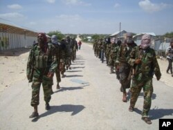 FILE - Members of Somalia's al- Shabab militant group patrol on foot on the outskirts of Mogadishu.