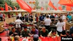 人們在新疆喀什老城區飄揚的中國國旗下吃飯 (2018年9月6日)