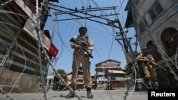 Indian policemen stand guard behind concertina wire during a strike called by separatists to mark the death anniversaries of chief cleric of Kashmir, Moulana Mohammad Farooq and Abdul Gani Lone, a Kashmiri separatist leader, in Srinagar, May 21, 2018.
