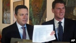 Australian Christian Lobby managing director Lyle Shelton, left, presents Australian Conservatives party leader Sen. Cory Bernardi, right, with 55,000 signatures on a petition at Parliament House in Canberra, Australia, Aug. 8, 2017. The petition demands a public vote on whether Australia should allow gay marriage.