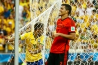 Brazil's Neymar holds the net after a failed attempt at the goal, as Mexico's Francisco Rodriguez smiles, during their 2014 World Cup Group A soccer match at the Castelao arena in Fortaleza June 17, 2014.
