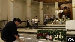 Seorang wanita menaruh lilin tanda berkabung bagi korban serangan warga Kristen di Baghdad, Irak.