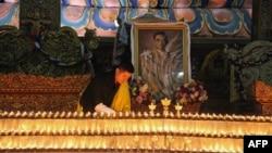 13일 태국 왕실이 푸미폰 아둔야뎃 국왕의 서거를 발표한 직후 이웃나라 부탄의 지그메 케사르 남기엘 왕추크 국왕이 왕궁 사찰에 푸미폰 국왕의 영정을 설치한 뒤 촛불을 밝히고 있다.
