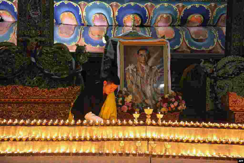 This photograph released by Bhutan's Royal Office for Media shows King Jigme Khesar lighting candles at the Kuenra of the Tashichhodzong in Thimpu next to a portrait of Thailand's King Bhumibol Adulyadej, who died in Bangkok.