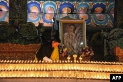 This photograph released on October 13, 2016 by Bhutan's Royal Office for Media on Bhutanese King Jigme Khesar's Facebook page shows King Jigme Khesar at the Kuenra of the Tashichhodzong in Thimpu lighting candles next to a portrait of Thailand's King Bhu