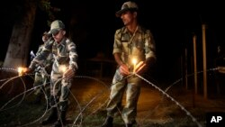 Indian Border Security Force soldiers place candles on a fence to celebrate Diwali, near the India-Pakistan international border area of Ranbir Singh Pora, about 33 kilometers (21 miles) from Jammu, India, Nov. 2, 2013.