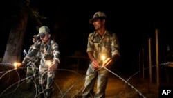 Petugas perbatasan di wilayah Ranbir Singh Pora, sekitar 33 kilometer dari kota Jammu, India, meletakkan lilin di pagar perbatasan India-Pakistan untuk persiapan perayaan Diwali (2/11).