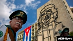 """Thành viên của ban nhạc quân đội đứng dưới tác phẩm điêu khắc bằng sắt của Ernesto """"Che"""" Guevara tại Quảng trường Cách mạng ở Havana, Cuba."""