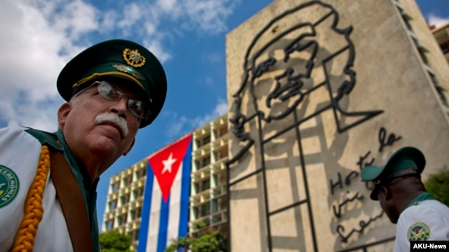 "FILE - Members of a military band stand under the iron sculpture of Ernesto ""Che"" Guevara at Revolution Square in Havana, Cuba"