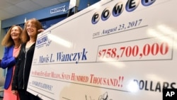 Mavis Wanczyk, of Chicopee, Mass., stands by a poster of her winnings during a news conference where she claimed the $758.7 million Powerball prize. (AP Photo/Steven Senne)