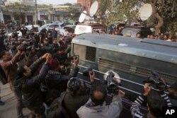 Surrounded by journalists and security forces, a prison van carrying Mohammad Imran, who is accused of the brutal killings of eight children in the eastern city of Kasur, arrives to a courthouse, in Lahore, Jan. 24, 2018. The Pakistani court has given police two weeks to interrogate the suspect.