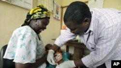Iren Salama (left) holds her baby Pendo as it is given a malaria vaccination in a medical trial at a clinic in the Kenya coastal town of Kilifi, Nov 23, 2010 (file photo)