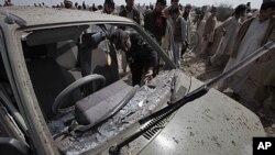 Cảnh sát và cư dân Pakistan xem xét một chiếc xe bị hư hại trong vụ đánh bom tự sát tại một đám tang ở ngoại ô Peshawar, ngày 11/3/2012