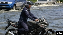 Seorang aparat di Thailand mengendarai sepeda motornya di tengah-tengah banjir yang masih merendam Bangkok, dekat Bandara Don Muang.