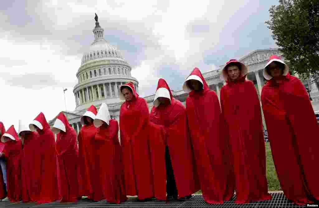 واشنگٹن میں خواتین، ایک ناول پر مبنی ٹی وی سیریز 'دی ہینڈ میڈز ٹیل' کا لباس زیب تن کیے ہوئے، جو ری پبلکن سینٹرز کی جانب سے 'پلانڈ پیرنٹ ہڈ' کو دی جانے والی امدادی رقم میں کٹوتی کے خلاف احتجاج کر رہی ہیں۔