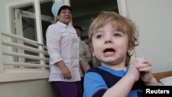 Adoption candidate Mark, 2, reacts in the children's department of a local hospital in Russia's Siberian city of Krasnoyarsk, March 23, 2011.
