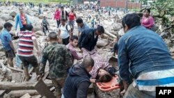 A handout picture released by the Colombian Army press office shows people helping to carry a woman after mudslides following heavy rains, in Mocoa, Putumayo, on April 1, 2017. (AFP PHOTO / EJERCITO DE COLOMBIA)