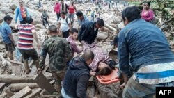 A handout picture released by the Colombian Army press office shows people helping to carry a woman after mudslides following heavy rains in Mocoa, April 1, 2017.