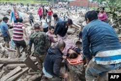 A handout picture released by the Colombian Army press office shows people helping to carry a woman after mudslides following heavy rains, in Mocoa, Putumayo, on April 1, 2017.