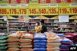 戴着口罩的顾客从泰国曼谷一家超市堆放大米的货架旁走过。泰国是世界最大的大米出口国。(2020年3月4日)