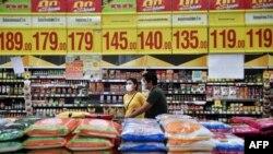 戴着口罩的顾客从泰国曼谷一家超市堆放大米的货架旁走过。(2020年3月4日)