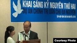 Cô Nancy Nguyễn tặng diễn giả Nguyễn Gia Kiểng chiếc nơ kỷ niệm cuộc xuống đường đòi dân chủ của sinh viên Hồng Kông. (Ảnh:Dân Huỳnh/Người Việt)