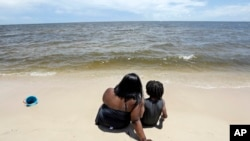 Tracey Gasper, left, and her son, Chase, 6, from Donaldsonville, La., sit in the sands of Biloxi Beach in Biloxi, Miss., May 26, 2018, as Subtropical Storm Alberto slowly makes its way through the Gulf of Mexico. The storm is threatening to bring heavy ra