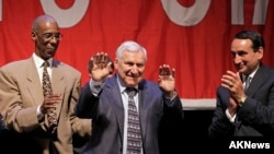 FILE - Former North Carolina basketball coach Dean Smith, center, waves as Duke coach Mike Krzyzewski, right, and former North Carolina player Charles Scott applaud during a ceremony presented by the North Carolina Sports Hall of Fame in Raleigh, N.C., Ju