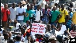 Para pengunjuk rasa membentangkan spanduk bertuliskan protes atas kunjungan Presiden Perancis di Haiti (12/5).