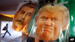 FILE - Facemasks depicting former Soviet dictator Josef Stalin and U.S President-elect Donald Trump hang on sale hours before Trump is to be sworn in as president of the United States, at a souvenir street shop in St. Petersburg, Russia, Jan. 20, 2017.