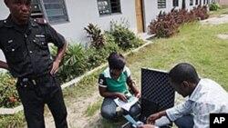 Wani Dansanda yake bada kariya ga jami'in hukumar zabe. (File Photo)