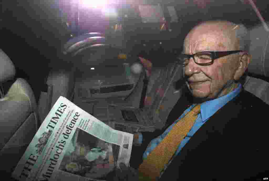 "News Corp Chief Executive and Chairman Rupert Murdoch holds a copy of T""he Times"" newspaper as he leaves his home in London, England, July 20, 2011. (Reuters)"