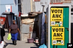 A woman, left, walks near an African National Congress, ANC, political poster fixed on a toilet door, that calls South Africans to vote during municipal elections in the township of Khayelitsha on the outskirts of Cape Town, South Africa, Tuesday, Aug. 1,