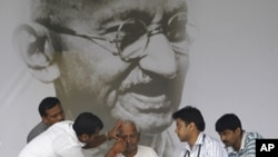 Veteran Indian social activist Anna Hazare (C) is examined by a team of doctors in front of a portrait of Mahatma Gandhi on the eighth day of his fasting at Ramlila grounds in New Delhi, Aug. 23, 2011.