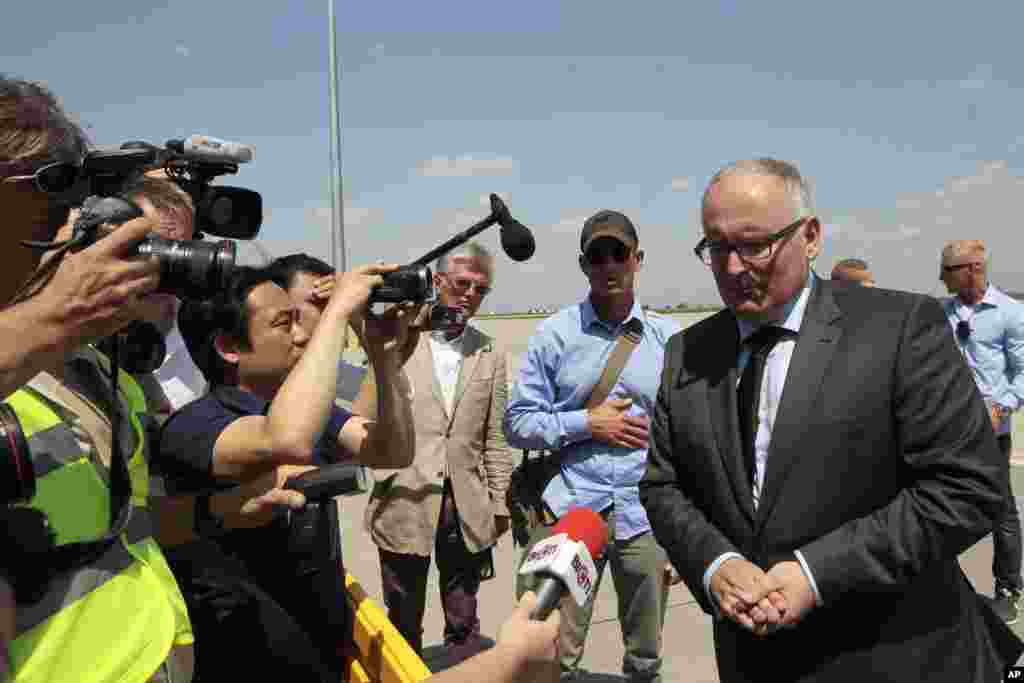 Netherlands Foreign Minister Frans Timmermans (right) speaks to the media while a Dutch military cargo plane with bodies of some of the passengers of the downed Malaysia Airlines jetliner leaves Ukraine for the Netherlands, July 25, 2014.