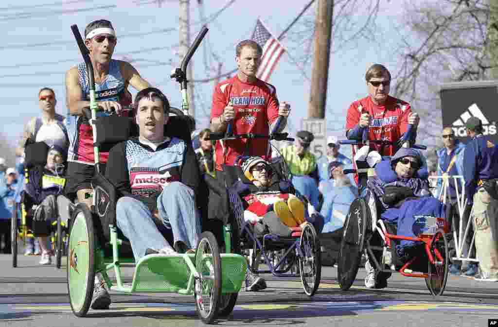 Participants in the wheelchair division of the 118th Boston Marathon start their race, in Hopkinton, Mass., April 21, 2014.