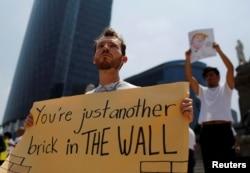 ຜູ້ປະທ້ວງຄົນນຶ່ງ ຖືປ້າຍປະທ້ວງ ທ່ານ Donald Trump ຜູ້ສະໝັກເປັນປະທານາທິບໍດີສະຫະລັດ ສັງກັດພັກ Republican ທີ່ ສະຖານທີ່ Angel of Independence ໃນນະຄອນ Mexico City, Mexico, 31 ສິງຫາ, 2016.