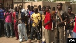 Members of a civilian defense group in Makary, Cameroon, arm themselves with bows and arrows. Authorities say such groups get support from soldiers in Cameroon's Rapid Intervention Brigade. (M.E. Kindzeka/VOA)