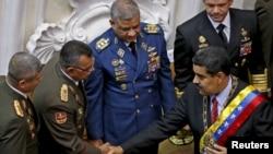 El presidente de Venezuela, Nicolás Maduro y Néstor Reverol, comandante general de la Guardia Nacional venezolana, se dan la mano durante su informe anual sobre el estado de la nación en la Asamblea Nacional de Caracas, Venezuela, el 15 de enero de 2016.