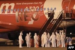 身穿防护服的泰国海军官员在乌塔堡国际机场站立在一架从中国武汉撤回侨民的飞机旁。(2020年2月4日)