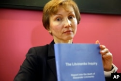 Marina Litvinenko, widow of former Russian spy Alexander Litvinenko, holds a copy of the report for the media during a press conference in London, Jan. 21, 2016.